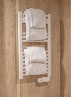 흰색 수건이 위에 접힌 흰색 금속 온난화 선반 뒤에 회색 샤워 벽이 있는 빈 욕실. 욕실의 라디에이터에 흰 수건