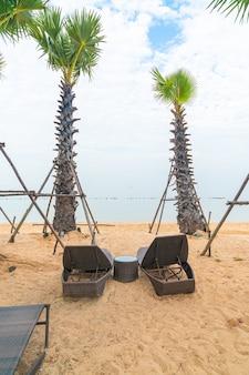海とビーチのヤシの木と空のビーチチェア