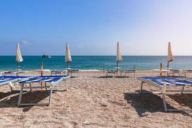 Пустые пляжные шезлонги ждут отдыхающих на красивом пляже.