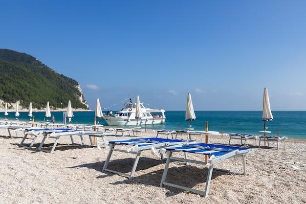 Пустые пляжные шезлонги ждут отдыхающих на красивом пляже
