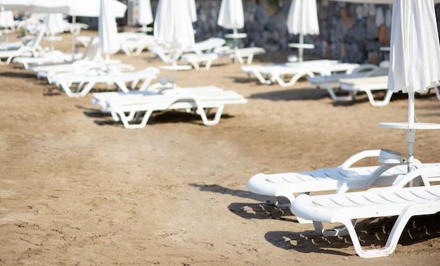 Пустой пляж с шезлонгами и закрытыми зонтиками во время вспышки вируса covid 19. концепция карантина. кризис туристического бизнеса. выборочный фокус.