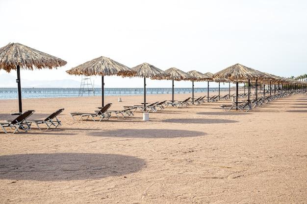 일광욕 용 의자와 우산이있는 빈 해변. 검역 중 관광 위기.