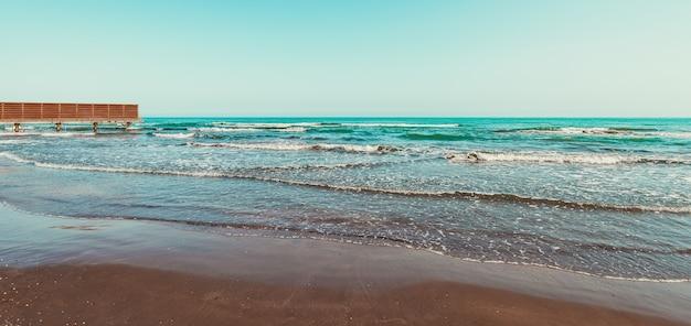 Пустой пляж с желтым песком и синими волнами на карантине на курорте