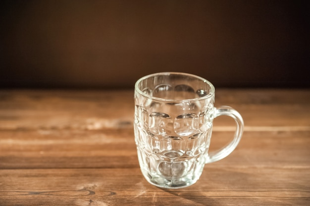 Empty beer glass close-up. empty beer mug on a dark background and copy space.