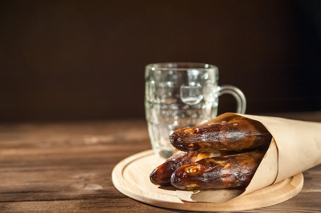 Empty beer glass and hot smoked fish close-up. empty beer mug and fish on a dark background and copy space.