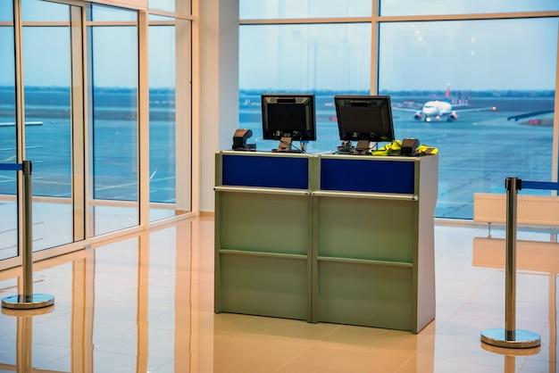 공항 앞 컴퓨터와 대기 줄이있는 빈 베이지 색 체크인 데스크