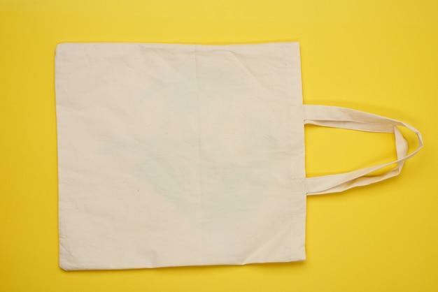 Пустой бежевый текстильный мешок на желтом, отказ от пластиковых пакетов, плоская планировка, нулевые отходы