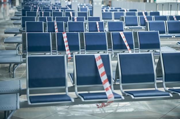国際空港の出発ホールにある空のベンチで、座席に保護テープが付いています