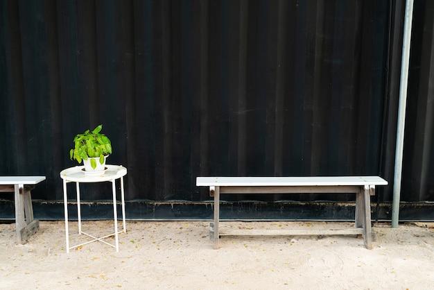 Пустая скамейка на фоне черной стены