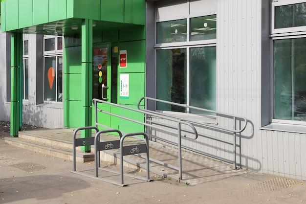 Пустая велосипедная стоянка возле магазина с пандусом для передвижения людей с ограниченными возможностями