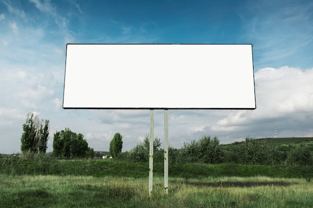 Empty billboard for advertising poster in green field omn background of blue sky.