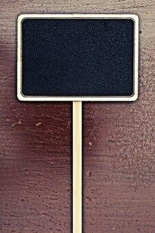 Пустая черная доска на деревянной панели