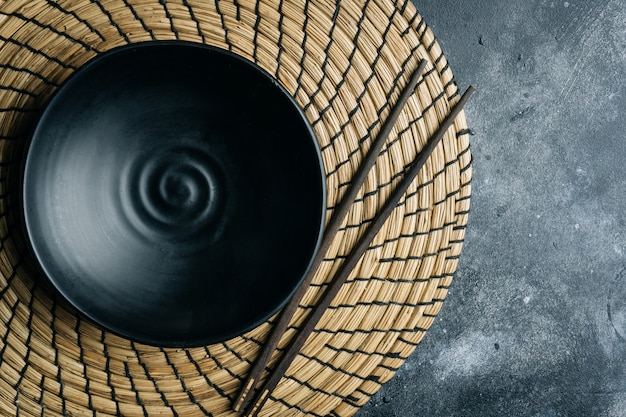 Empty black bowl (ceramic handmade) with chinese chopsticks on a gray stone