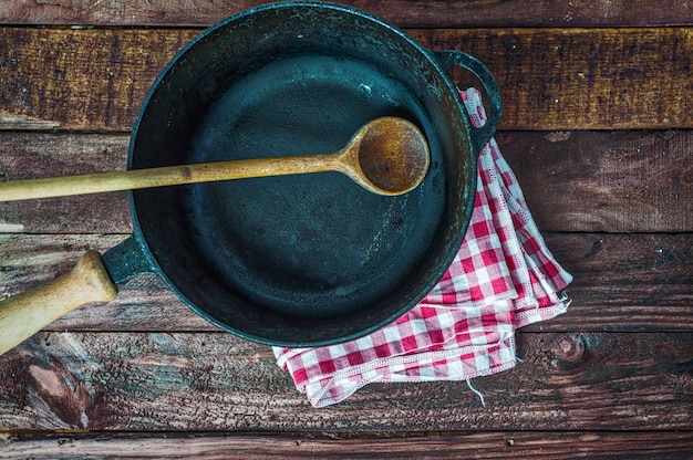 Empty black cast-iron frying pan with a wooden handle on a brown surface