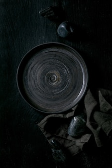 검은 나무 배경 위에 섬유 냅킨에 주위에 검은 돌으로 빈 블랙 세라믹 플레이트. 평평하고 공간.