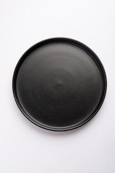 空の黒いセラミック ラウンド プレートまたは白い表面に分離されたトレイ