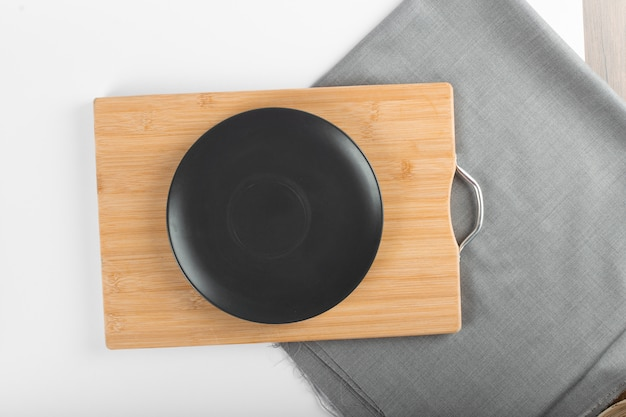 An empty black ceramic saucer