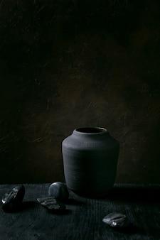 장식 돌으로 검은 나무 테이블에 빈 블랙 세라믹 꽃병. 어두운 정물. 공간을 복사하십시오.