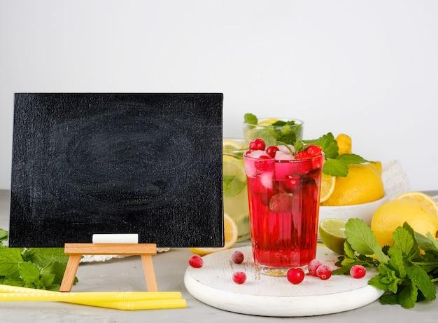 夏のドリンクレシピとベリーレモネードのグラスを書くための空の黒いチョークボード