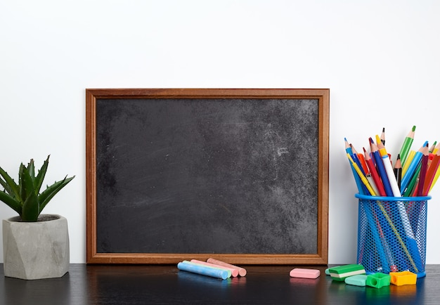 Empty black chalk board, multi colored pencils in a blue metal stand on a black table