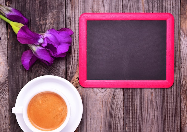 Empty black chalk board and white cup with cappuccino