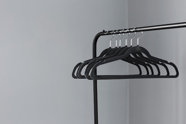 灰色の壁の背景に空の黒いハンガー