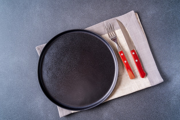 Empty black and cutlery plate over napkin on brown wooden table top view, copy space for text.
