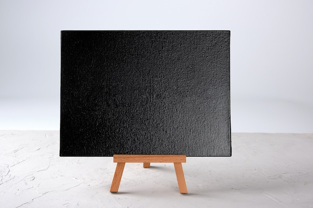 Empty black frame stands on a wooden tripod