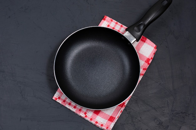 赤い市松模様のナプキンに空の黒いフライパンまたはフライパン