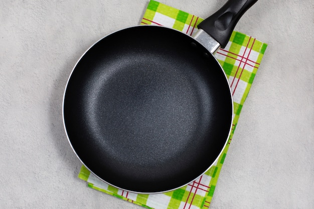 Empty black frying pan with green kitchen towel