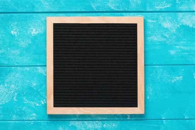 Empty black letterboard on blue wooden table.
