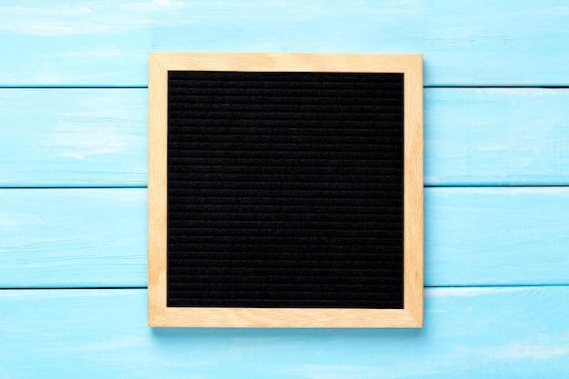 青い木製のテーブルの上の空の黒い文字板