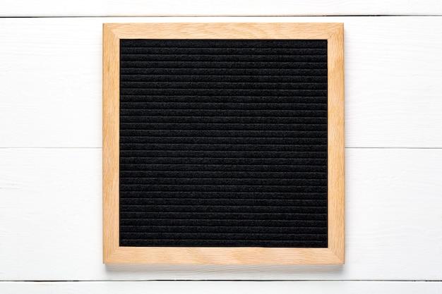 白い木の背景に空の黒い文字板。モックアップをデザインします。