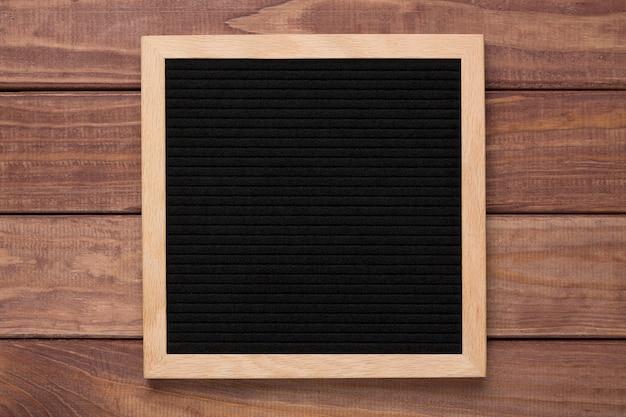Empty black letterboard on wood.