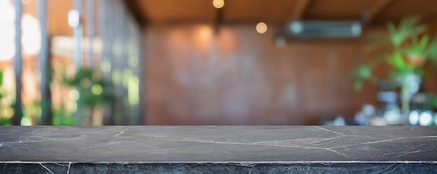 空の黒い大理石の石のテーブルトップとぼやけたコーヒーショップ