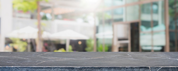 Empty black marble stone table top and blurred restaurant exterior banner background