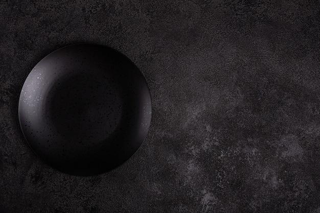 An empty black matte ceramic plate on a dark black background. copyspace