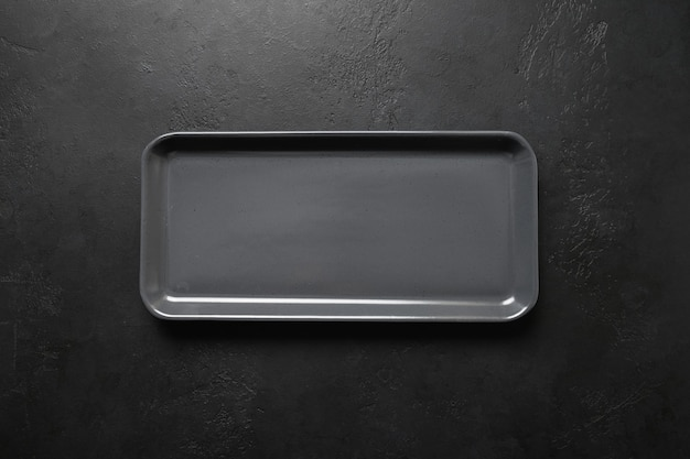 Empty black modern rectangular plate on black background, kitchen stuff, flat lay for cooking as background.