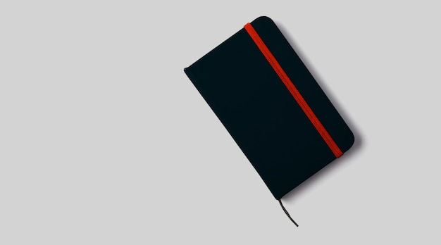 Empty black notebook mockup with soft shadows on neutral grey concrete background.