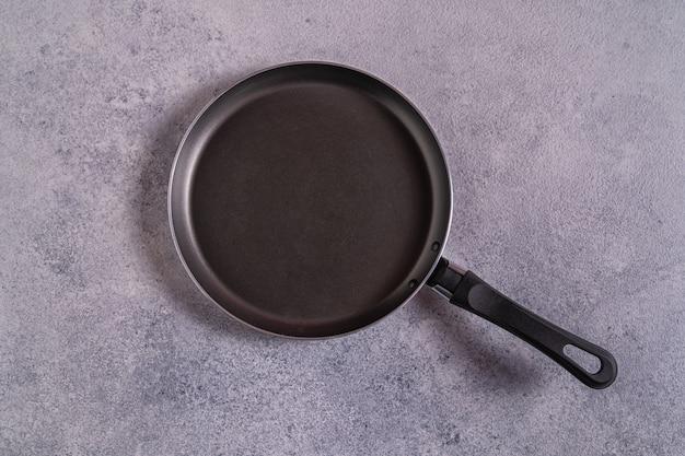 Пустая черная сковорода на сером столе