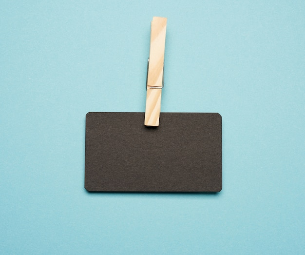 木製洗濯はさみで空の黒い紙長方形の名刺