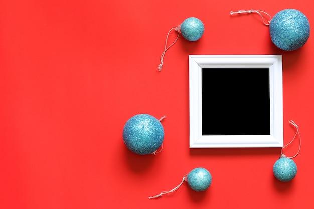 赤い背景に空の黒のフォトフレームとクリスマスの装飾。