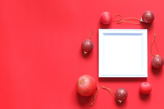 Empty black photo frame and christmas decoration on red background.