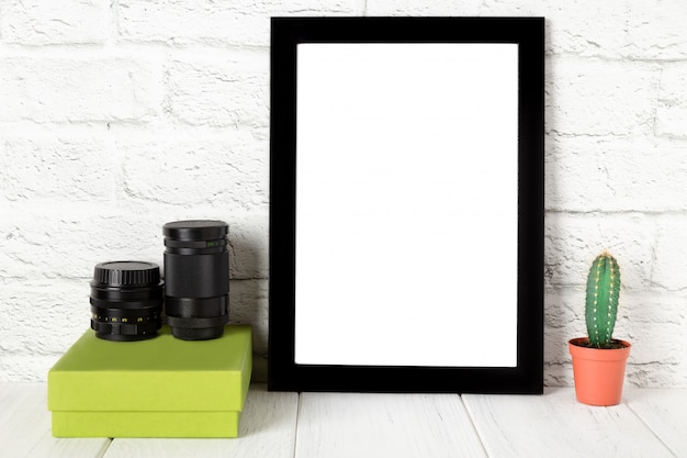 Empty black photo frame on wooden shelf or table. mockup with copy space.