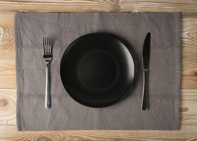 コピースペースのある木製のテーブルトップビューに空の黒いプレートとカトラリー。