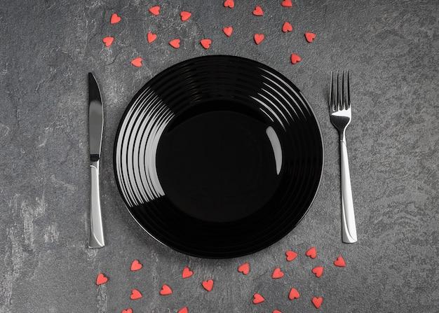 Пустая черная тарелка и столовое серебро на черном каменном столе, украшенном на день святого валентина