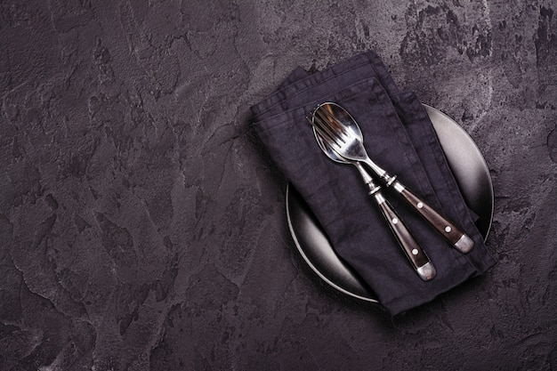 Опорожните черную плиту и silverware на темном каменном backgroun. вид сверху