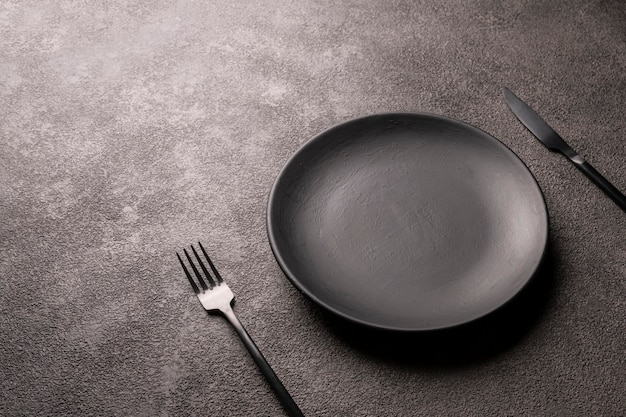 Пустая черная тарелка, вилка и нож на темном столе