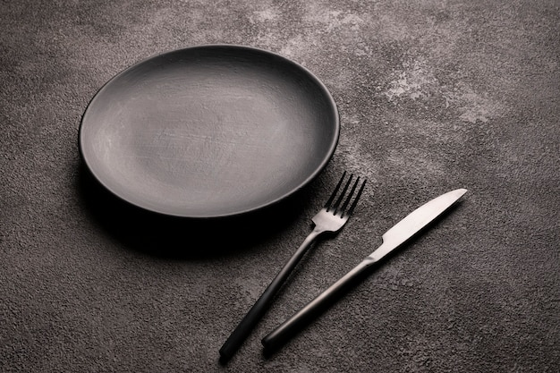 Empty black plate, fork and knife on a dark table