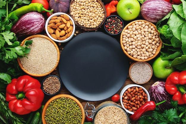 穀物、野菜の背景の空の黒い皿。健康的なビーガンフードのコンセプトです。